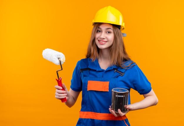 Operaio del costruttore della giovane donna in uniforme della costruzione e casco di sicurezza che tiene il barattolo di vernice e sorridere del rullo