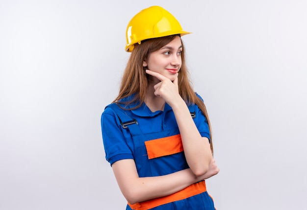 Young woman builder worker in construction uniform and safety helmet looking aside  standing with hand on chin with pensive expression thinking over white wall