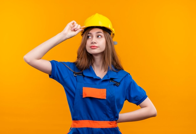 Young woman builder worker in construction uniform and safety helmet looking aside with confident look touching her helmet standing