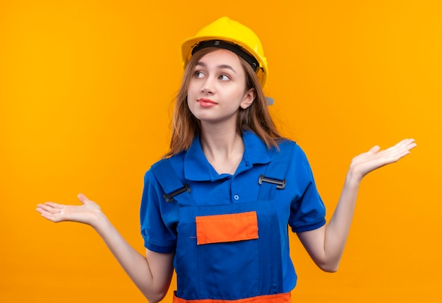 Operaio del costruttore della giovane donna in uniforme della costruzione e casco di sicurezza che sembra sorridere confuso che scrolla le spalle le spalle, avendo nessuna risposta in piedi