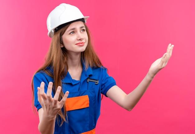 Operaio del costruttore della giovane donna in uniforme da costruzione e casco di sicurezza che sembra deluso alzando le mani in piedi sopra la parete rosa