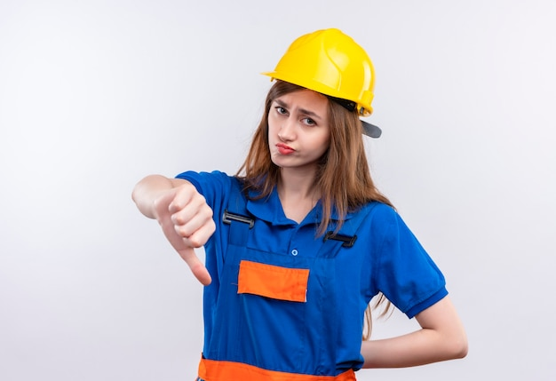 Young woman builder worker in construction uniform and safety helmet looking displeased showing thumbs down standing over white wall