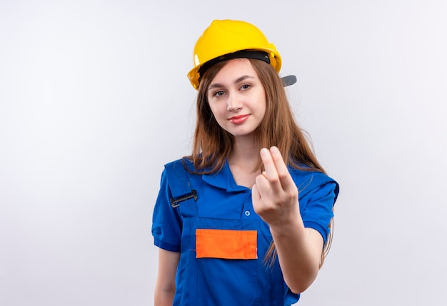 Young woman builder worker in construction uniform and safety helmet making come in gesture with hand looking confident standing over white wall