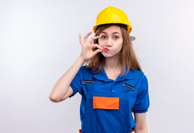 Young woman builder worker in construction uniform and safety helmet making silence gesture like closing mouth with a zipper standing over white wall