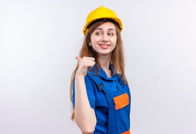 Young woman builder worker in construction uniform and safety helmet pointing with thumb to the side smiling confident standing over white wall