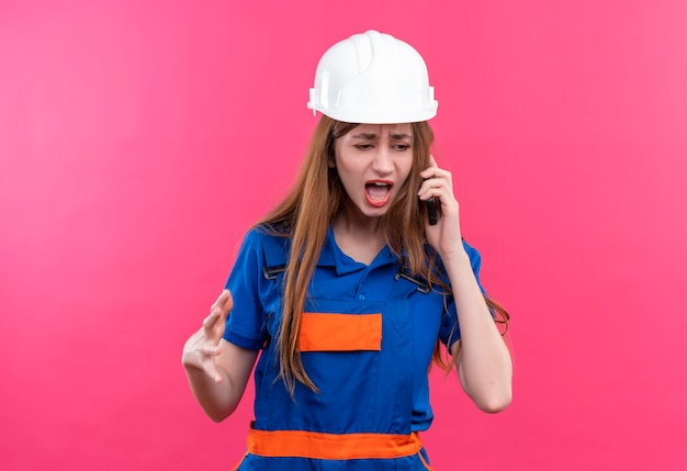 Young woman builder worker in construction uniform and safety helmet shouting with annoyed expression  while talking on mobile phone standing over pink wall