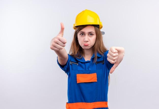 Operaio del costruttore della giovane donna in uniforme della costruzione e casco di sicurezza che mostra i pollici su e giù che stanno sopra il muro bianco