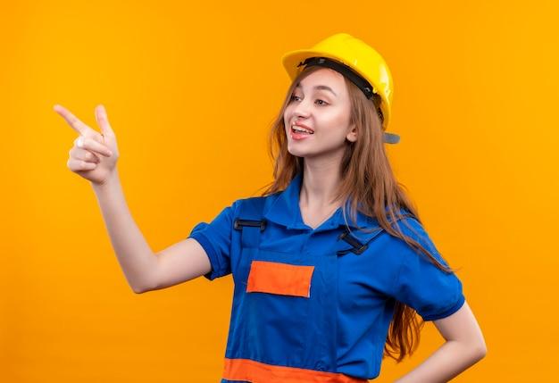 Operaio del costruttore della giovane donna in uniforme della costruzione e casco di sicurezza che sorride allegramente indicando con il dito indice al lato che sta sopra la parete arancione