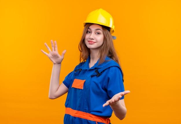 Operaio costruttore di giovane donna in uniforme da costruzione e casco di sicurezza sorridente amichevole rendendo gesto di benvenuto ampia apertura mani in piedi sopra la parete arancione