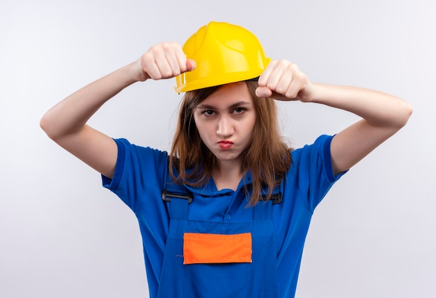 白い壁の上に立っている眉をひそめている顔で見ている建設制服と安全ヘルメットの握りこぶしで若い女性ビルダー労働者