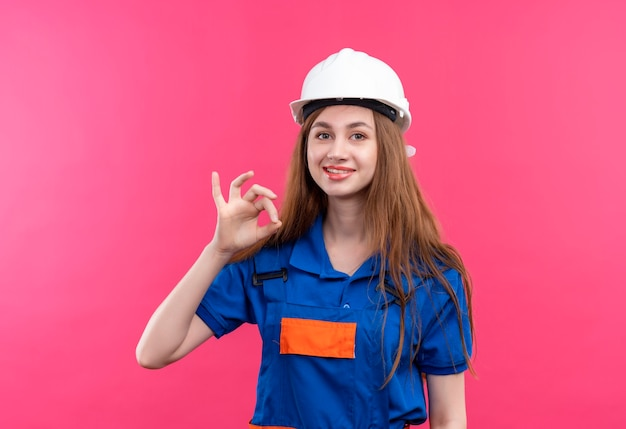 建設制服と安全ヘルメットの若い女性ビルダー労働者ピンクの壁の上に立っているokサインを示す幸せで前向きな笑顔