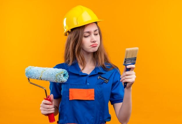 Молодая женщина-строитель в строительной форме и защитном шлеме держит кисть и малярный валик, глядя на кисть со скептическим выражением лица, стоя над оранжевой стеной