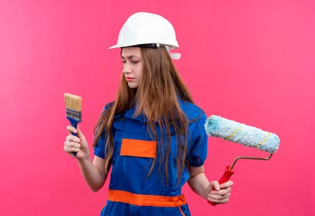 Молодая женщина-строитель в строительной форме и защитном шлеме, держащая кисть и малярный валик, смотрит на кисть со скептическим выражением лица, стоящим над розовой стеной