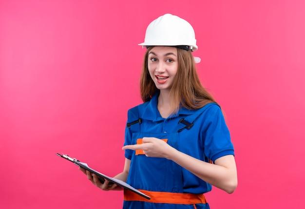 ピンクの壁の上に立って笑顔でそれに指で指しているクリップボードを保持している建設制服と安全ヘルメットの若い女性ビルダー労働者