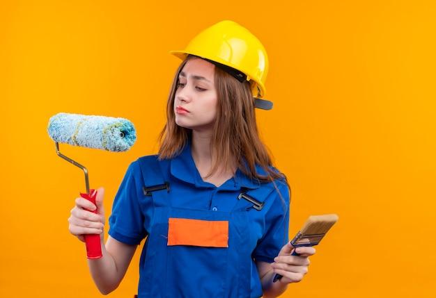 オレンジ色の壁の上に立っている懐疑的な表情でローラーを見てペイントローラーとブラシを保持している建設制服と安全ヘルメットの若い女性ビルダー労働者