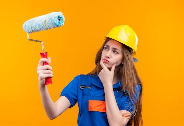 オレンジ色の壁の上に立っていると考えて、懐疑的な表情でローラーを見てペイントローラーとブラシを保持している建設制服と安全ヘルメットの若い女性ビルダー労働者