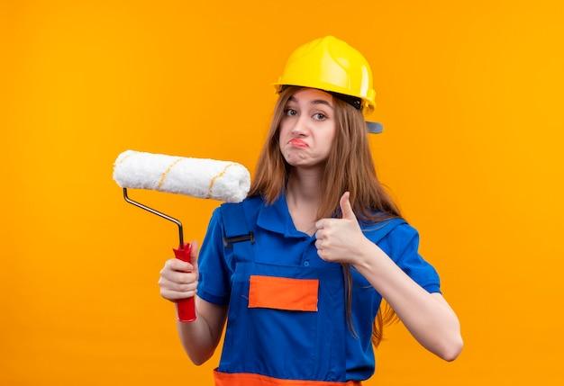 Молодая женщина-строитель в строительной форме и защитном шлеме держит валик с краской, показывает палец вверх, стоя над оранжевой стеной