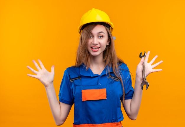 オレンジ色の壁の上に立って笑顔で降伏の手を上げるレンチを保持している建設制服と安全ヘルメットの若い女性ビルダー労働者