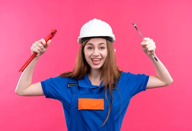 ピンクの壁の上に広く立って笑って腕を上げてレンチを保持している建設制服と安全ヘルメットの若い女性ビルダー労働者