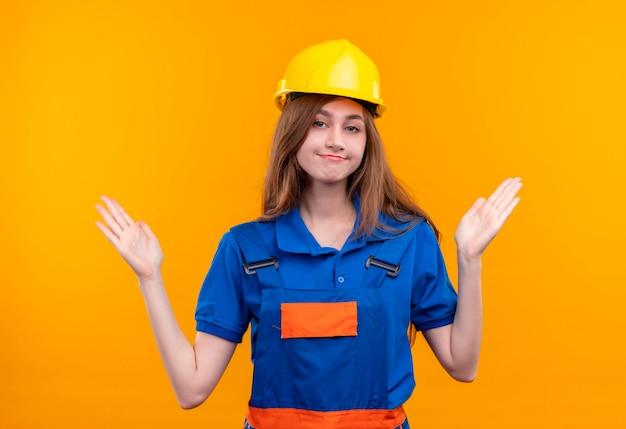 建設制服と安全ヘルメットの若い女性ビルダー労働者が立っている側に腕を広げて混乱しているように見える