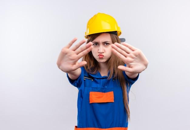 건설 유니폼과 안전 헬멧에 젊은 여자 작성기 노동자는 흰 벽에 정지 신호를 만드는 오픈 손으로 서 불쾌감을 찾고
