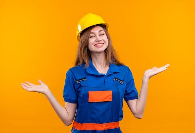建設制服と安全ヘルメットの若い女性ビルダー労働者は立って笑って横に腕を広げて探しています