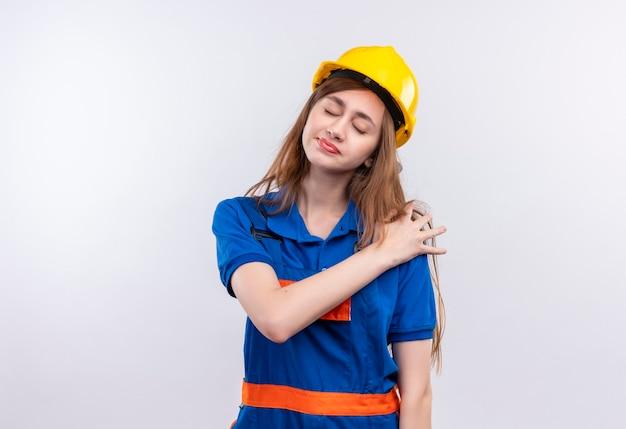 白い壁の上に立っている痛みを感じて肩に触れて疲れているように見える建設制服と安全ヘルメットの若い女性ビルダー労働者