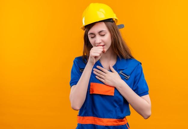 Молодая женщина-строитель в строительной форме и защитном шлеме, выглядящая нездоровой и кашляющей стоя