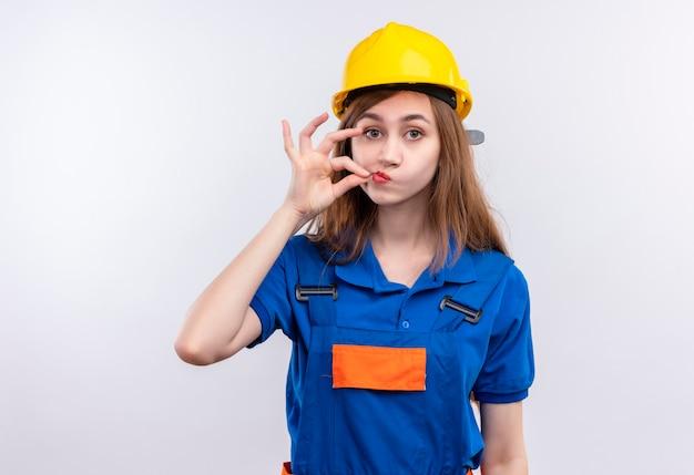 건설 유니폼 및 안전 헬멧에 젊은 여자 작성기 작업자 흰 벽 위에 서있는 지퍼로 입을 닫는 것과 같은 침묵 제스처를 만드는