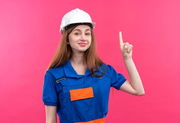 Молодая женщина-строитель в строительной форме и защитном шлеме, указывая пальцем вверх, имея отличную идею, улыбаясь, стоя над розовой стеной