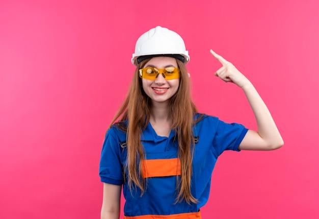 Молодая женщина-строитель в строительной форме и защитном шлеме, указывая указательным пальцем в голову