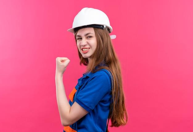 건설 유니폼 및 안전 헬멧에 젊은 여자 작성기 노동자 자신감을 찾고 주먹을 제기, 분홍색 벽 위에 서있는 승자처럼 포즈