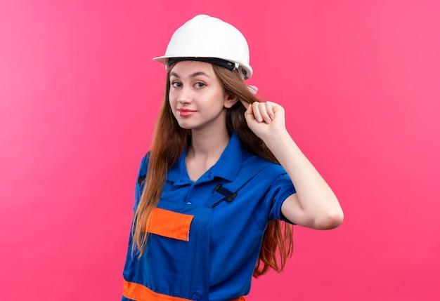 Молодая женщина-строитель в строительной форме и защитном шлеме, поднимая кулак, выглядит уверенно, концепция победителя стоит над розовой стеной