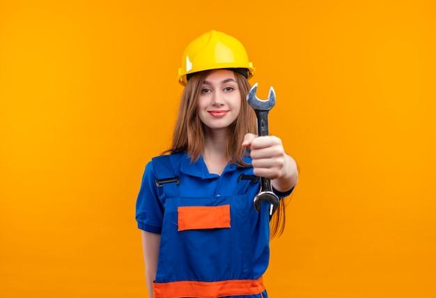Молодая женщина-строитель в строительной форме и защитном шлеме показывает гаечный ключ, уверенно смотрит, стоя над оранжевой стеной