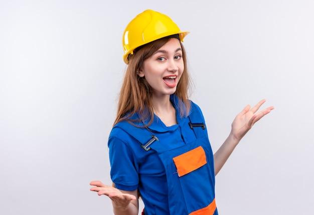 白い壁の上に立っている側に腕を広く広げて笑っている建設制服と安全ヘルメットの若い女性ビルダー労働者