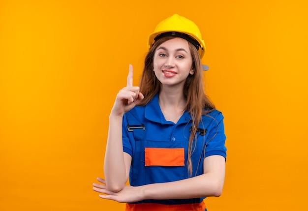 Молодая женщина-строитель в строительной форме и защитном шлеме, уверенно улыбаясь, указывая указательным пальцем вверх, имея хорошую идею, стоя над оранжевой стеной