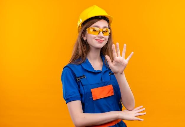 オレンジ色の壁の上に立っている手で自信を持って手を振って笑顔の建設制服と安全ヘルメットの若い女性ビルダー労働者