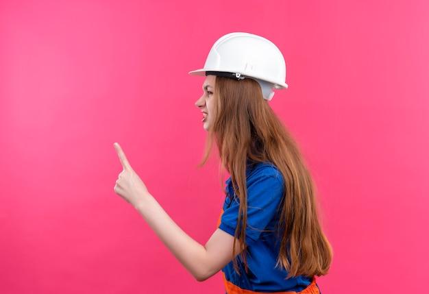 ピンクの壁に人差し指を上に向けて横向きに立っている建設制服と安全ヘルメットの若い女性ビルダー労働者