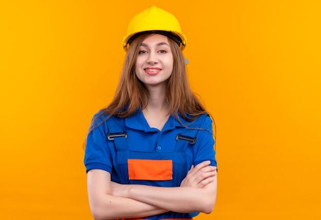 オレンジ色の壁の上の顔に自信を持って笑顔で見て腕を組んで立っている建設制服と安全ヘルメットの若い女性ビルダー労働者