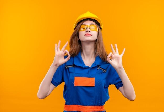 オレンジ色の壁に指で瞑想ジェスチャーを作ってリラックスして目を閉じて立っている建設制服と安全ヘルメットの若い女性ビルダー労働者