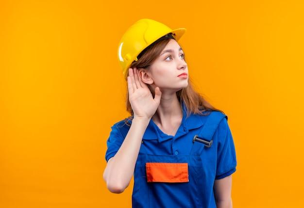 オレンジ色の壁の上に立って耳を傾けようとしている耳の近くの手で立っている建設制服と安全ヘルメットの若い女性ビルダー労働者