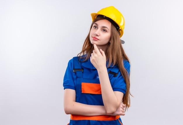 白い壁を考えて物思いにふける表情で顎に手で立っている建設制服と安全ヘルメットの若い女性ビルダー労働者