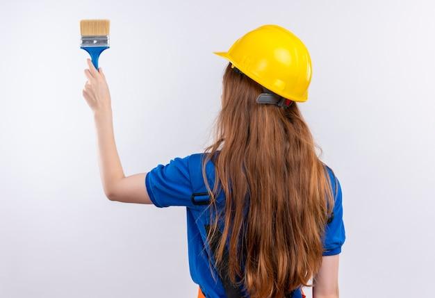 白い壁にペイントブラシを持って背中を持って立っている建設制服と安全ヘルメットの若い女性ビルダー労働者