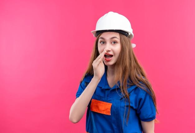 ピンクの壁の上に立っている口の近くの手で秘密を告げる建設制服と安全ヘルメットの若い女性ビルダー労働者