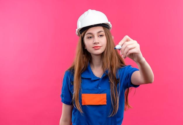 ピンクの壁の上に立っているペンで空中で何かを書き込もうとしている建設制服と安全ヘルメットの若い女性ビルダー労働者