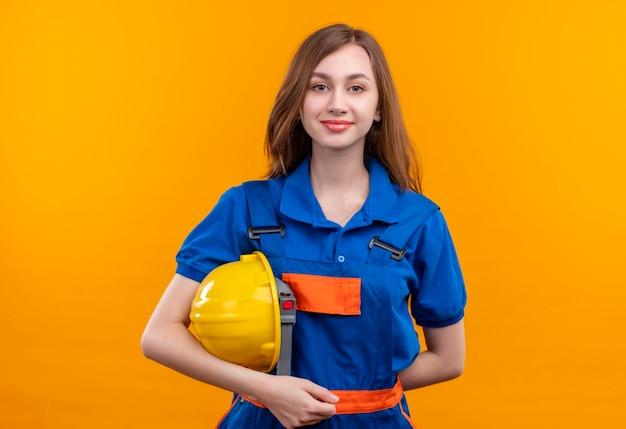 オレンジ色の壁の上に立って自信を持って見える安全ヘルメットを保持している建設制服の若い女性ビルダー労働者