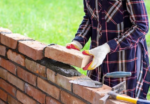 若い女性はレンガの壁を構築し、セメント砂モルタルにレンガを置きます