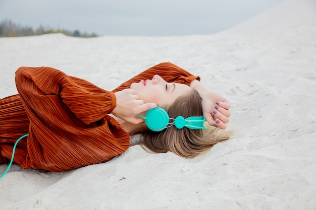 Young woman in burgundy color blouse with headphones lying down