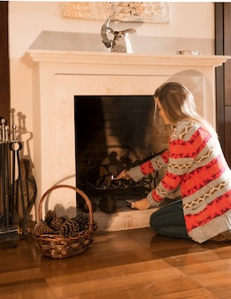 Young woman burning fireplace with matchstick at home