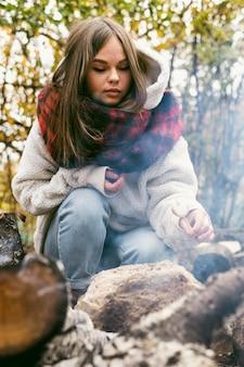 Giovane donna che brucia marshmallow nel fuoco di campo all'aperto